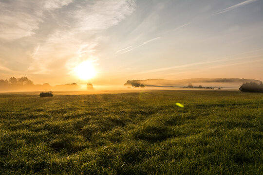 Beautiful sunset in rural landscape with sun rays shining through the morning fog
