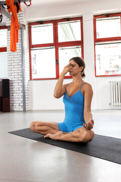 Woman meditating while doing yoga and sitting on the floor, chakra cleaning