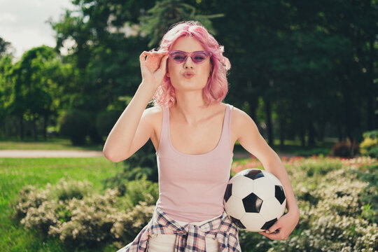 Photo of young sporty girl happy positive smile pouted lips send air kiss flirty hold football play outdoors