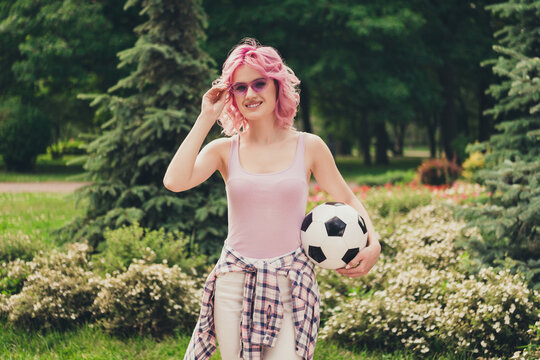 Photo of young sportive girl happy positive smile hold soccer ball player game park nature hand touch sunglass outdoors