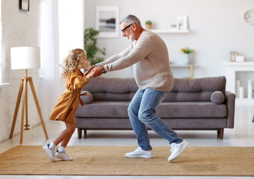 Active senior grandfather enjoying dance with cute little granddaughter in living room at home