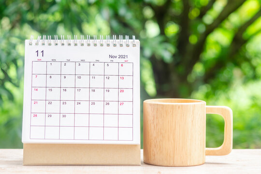 November month, Calendar desk 2021 for organizer to planning and reminder on wooden table with green nature background.