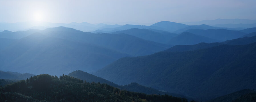 Panorama of dark blue mountain landscape in fog. Horizontal image.