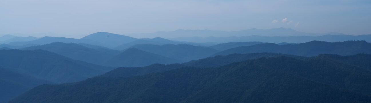 Beautiful dark blue mountain landscape of mountains. Horizontal panorama.