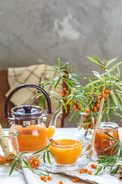 Cup and teapot of hot spicy tea with sea buckthorn, jam in the glass jar, branches of fresh berries on light wooden table surface in the rustic room