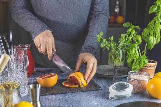 Woman hands cut grapefruit of knife on cutting board