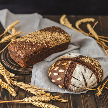 Gluten free food. Two healthy loaves of bread with grain and ears on dark table. Gluten free rye bread