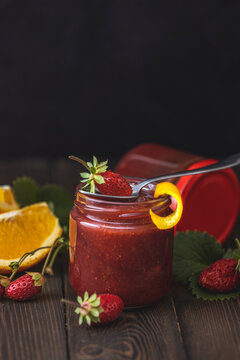 Homemade strawberry jam or marmalade with orange in the glass jar and ripe strawberries on the wooden table