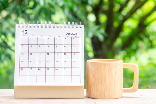 December month, Calendar desk 2021 for organizer to planning and reminder on wooden table with green nature background.