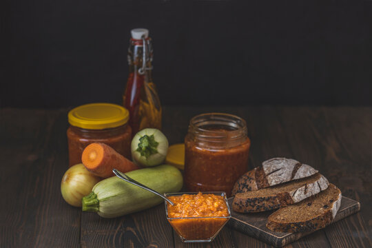 Squash zucchini paste or caviar and rye bread surrounded by the ingredients on dark wooden table