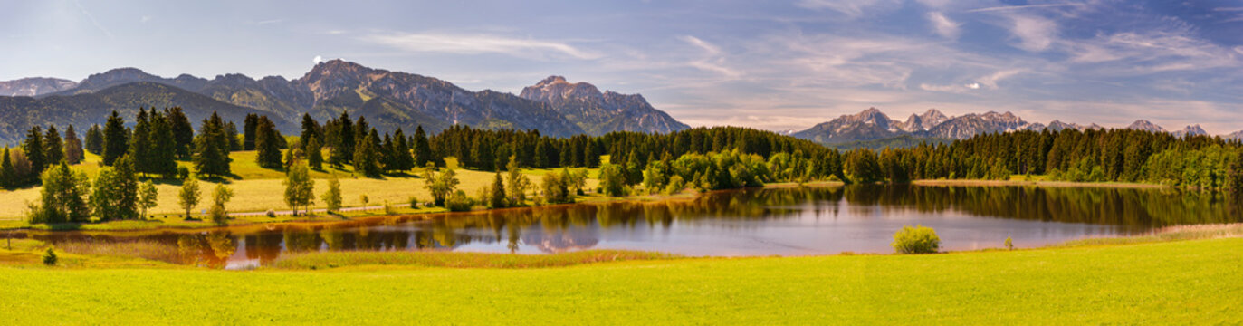 panoramic landscape in region Allgaeu with mountain range, lake and maedow