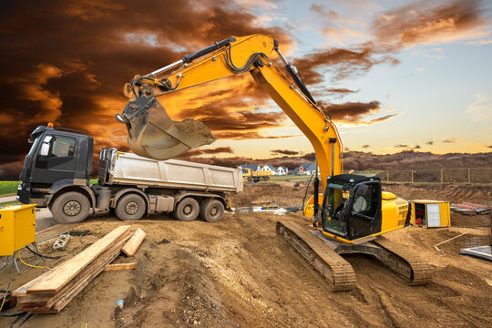 excavator working on construction site with dramatic clouds on sky