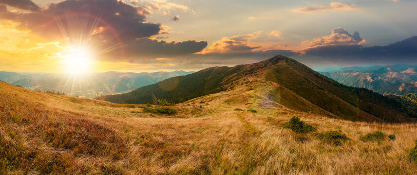 mountain landscape in early autumn at sunset. colorful scenery with peak and grassy hills in evening light. ridge in the distance beneath a cloudy sky. travel destination concept