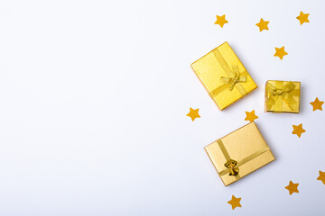 Composition of gold presents with stars and copy space on white background
