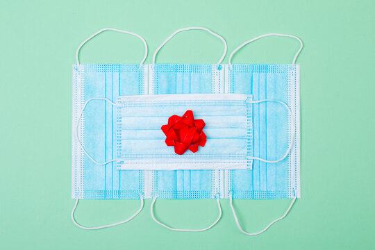 Composition of face masks with red ribbon on green background