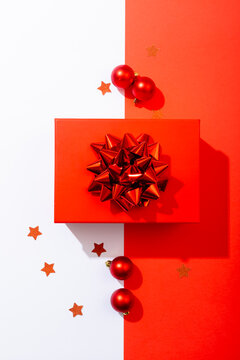 Composition of red christmas present with baubles on white and red background