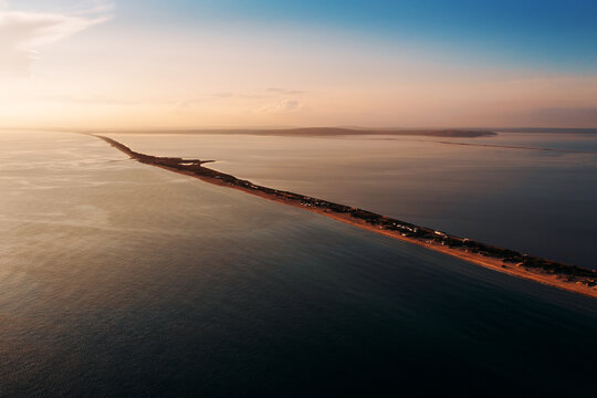Long spit with sandy beach between sea and liman at sunset, aerial view from drone.
