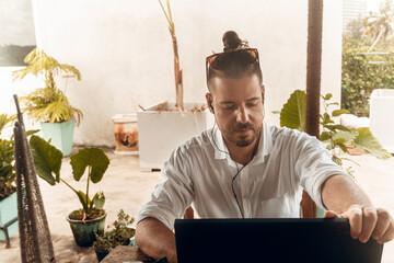Fototapeta Mężczyzna, cyfrowy nomada pracujący z laptopem i telefonem przy stoliku w kawiarni, praca zdalna podczas podróży. obraz