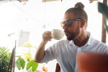 Mężczyzna pijący kawę w kawiarni w słoneczny dzień.
