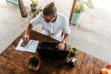 Fototapeta Mężczyzna pracujący przy laptopie z telefonem, praca zdalna podczas podróży, cyfrowy nomada w kawiarni. obraz