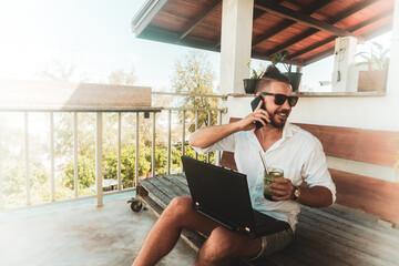 Fototapeta Mężczyzna, cyfrowy nomada pracujący z laptopem i rozmawiający przez telefon komórkowy w słoneczny dzień. obraz