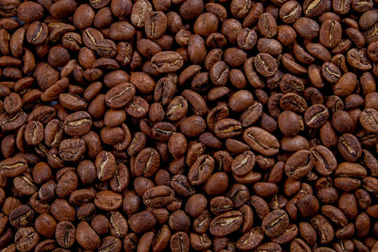 Macro shot of roasted brown coffee beans with a lot of copy space for text. Flat lay composition. Close up, top view, background.