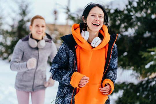 Tenacity and perseverance concept. Two young 30s women runner jogging in snow. Two females with positive emotion in warm sportswear running in a city park