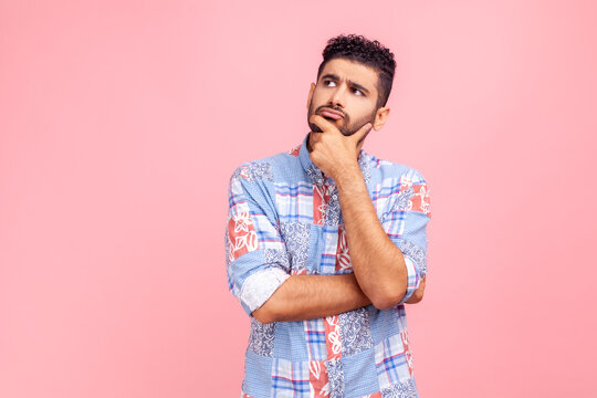 Pensive bearded man wearing blue casual style shirt holding chin with hand, need to think, planning strategy, thinking over ideas for startup. Indoor studio shot isolated on pink background.
