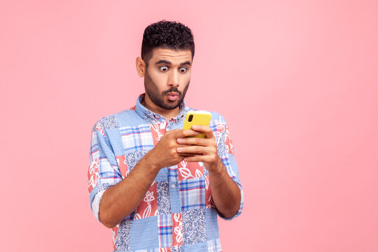 Mobile connection. Portrait of shocked astonished man in blue shirt reading post on social network using cell phone, chatting looking surprised. Indoor studio shot isolated on pink background.