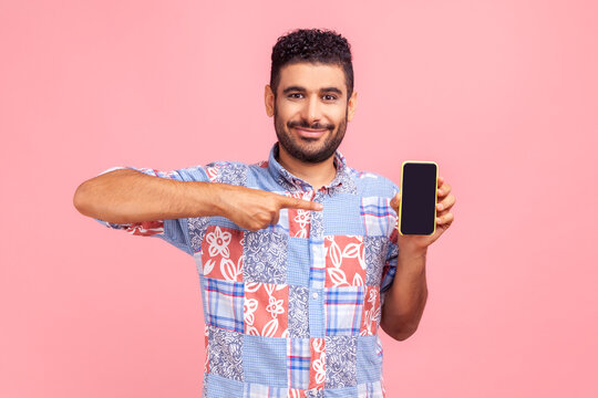 Happy cheerful beaded man in blue casual shirt shirt pointing finger at smartphone with empty screen, looking at camera with smile, freespace for adv. Indoor studio shot isolated on pink background.