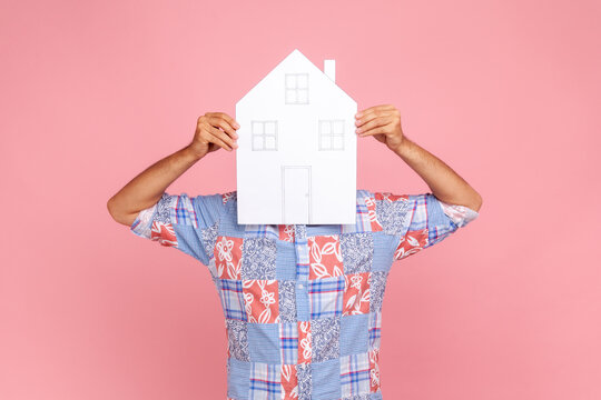 Unknown male person in blue casual style shirt covering his face with big paper house, dreams about own accommodation, estate agent. Indoor studio shot isolated on pink background.
