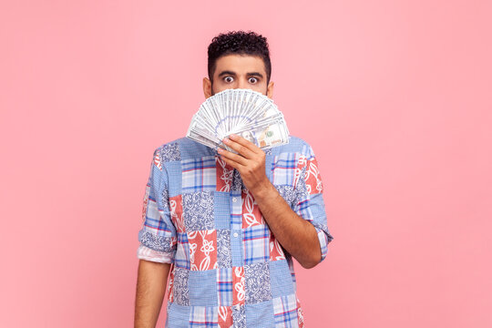Portrait of surprised attractive man with beard wearing blue casual shirt showing many cash dollars, covering mouth, looking at camera with big eyes. Indoor studio shot isolated on pink background.