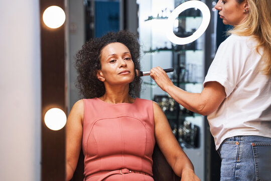 Delighted curly haired female being in beauty salon