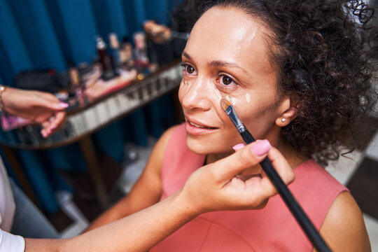 Delighted client doing professional makeup in salon