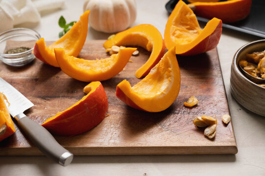 Top view of fresh, orange pumpkin slices on cutting board. Cooking ingredients for a butternut soup, pie or autumn foods.