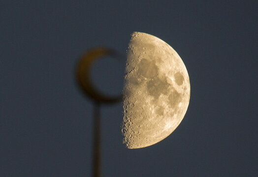 The moon is seen behind a mosque in the city of Almaty