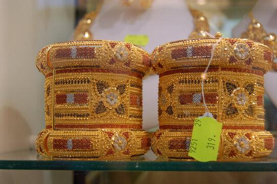 Ornate gold cuff bangles on display in a Tripoli Jewellery Shop