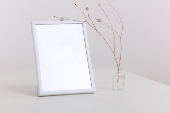 Empty picture frame and vase with dry flowers . Minimalist style home interior decoration. Simple and Elegant design. Copy space image, flat lay.