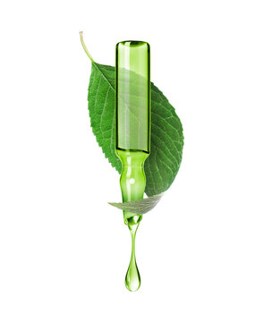 A drop drips from an ampoule on the background of a green leaf