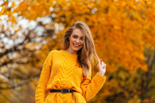 Smiling stylish happy woman with sweet smile in vintage knitted sweater walks in autumn park with golden fall leaves