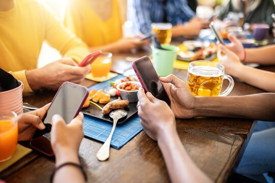 Group of young people using mobile phone while sitting on a terrace - Multiracial friends addicted by smart phone device sharing content in social media app - Millennial and technology concept