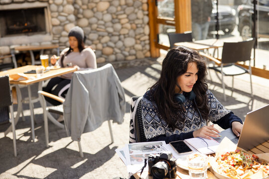 Woman working on laptop outside restaurant