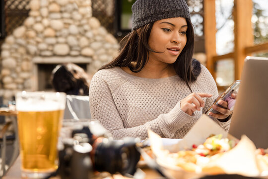Woman working on laptop and phone outside restaurant