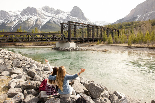 Friends sitting on river bank in front of mountain