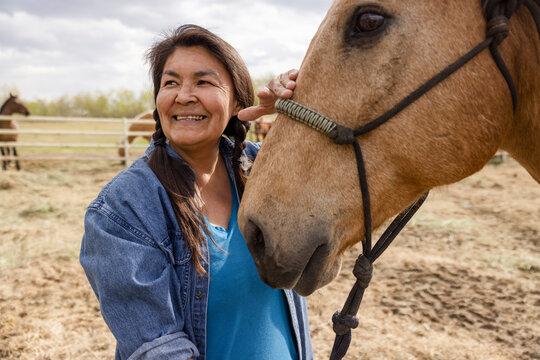 Happy female farmer with horse on farm