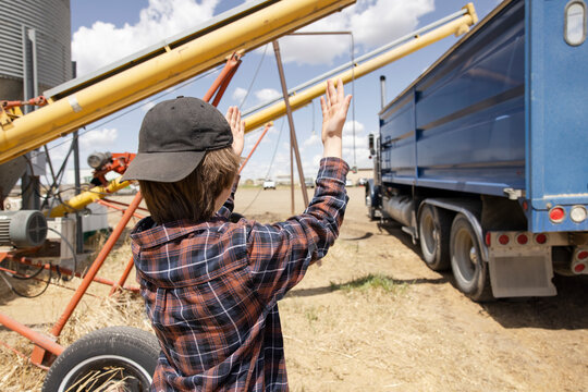 Boy guiding tractor trailer on sunny farm