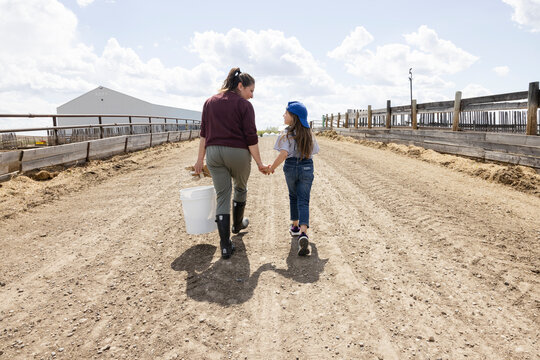 Mother and daughter farmers holding hands walking on sunny farm road