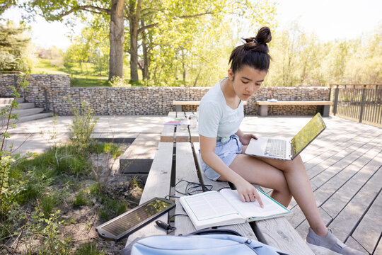 Girl reading and using laptop on park bench