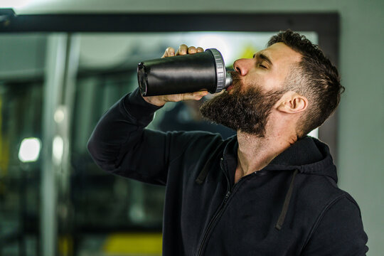 Front view portrait of young caucasian man athlete in black hoodie male standing in the gym holding protein supplement shaker supplementation in training waist up black hair and beard copy space drink