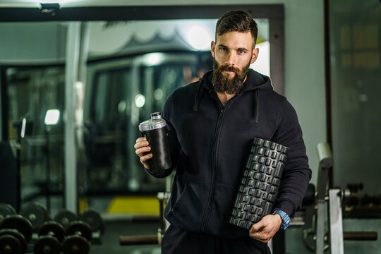 Front view portrait of male athlete standing at gym holding protein shaker and foam massage roller copy space